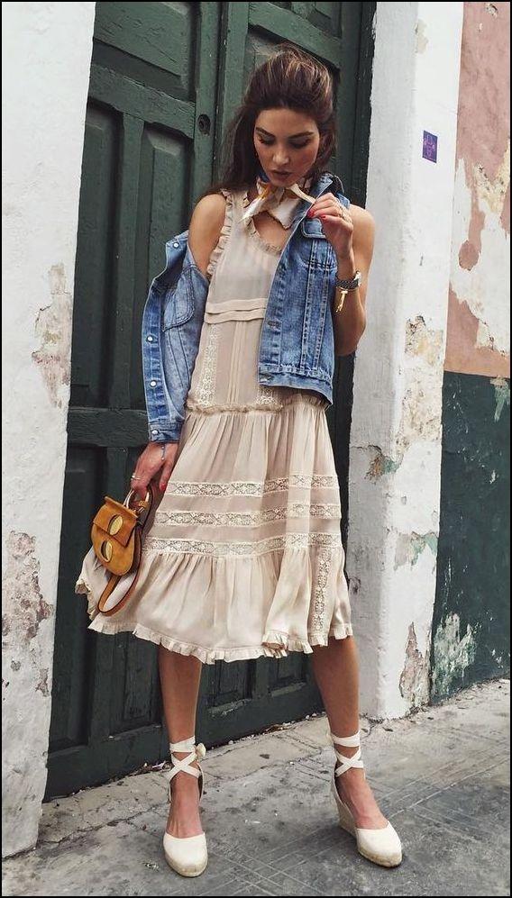 Młoda dziewczyna w pięknej koronkowej sukience, jeansowej kamizelce i espadryle na koturnie