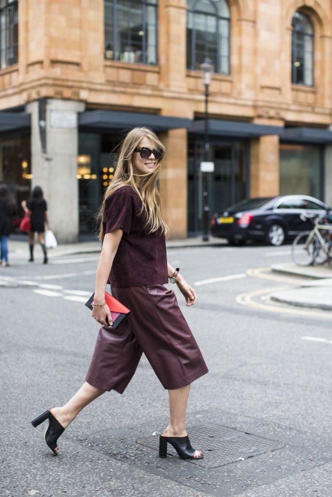 elegancka kobieta w bordowych spodniach z letnimi butami na słupku