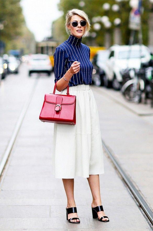 elegancka kobieta w czarnych butach na obcasie z czerwoną torebką