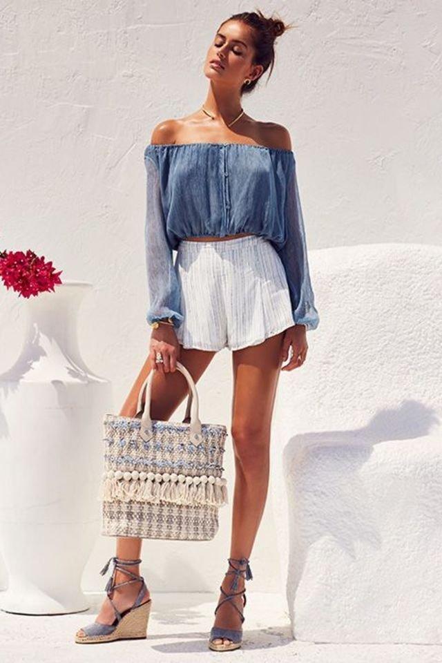 letnia stylizacja ładna kobieta w słonecznym miejscu o białych ścianach w espadrylach na koturnie, z torebką z frędzlami, w białych, krótkich spodenkach i niebieskiej bluzce z odsłoniętymi ramionami