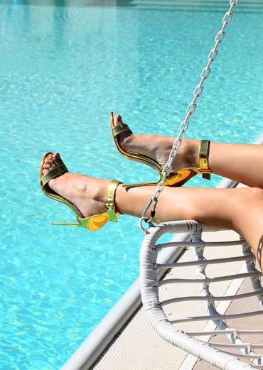 nogi w złotych sandałach nad basenem